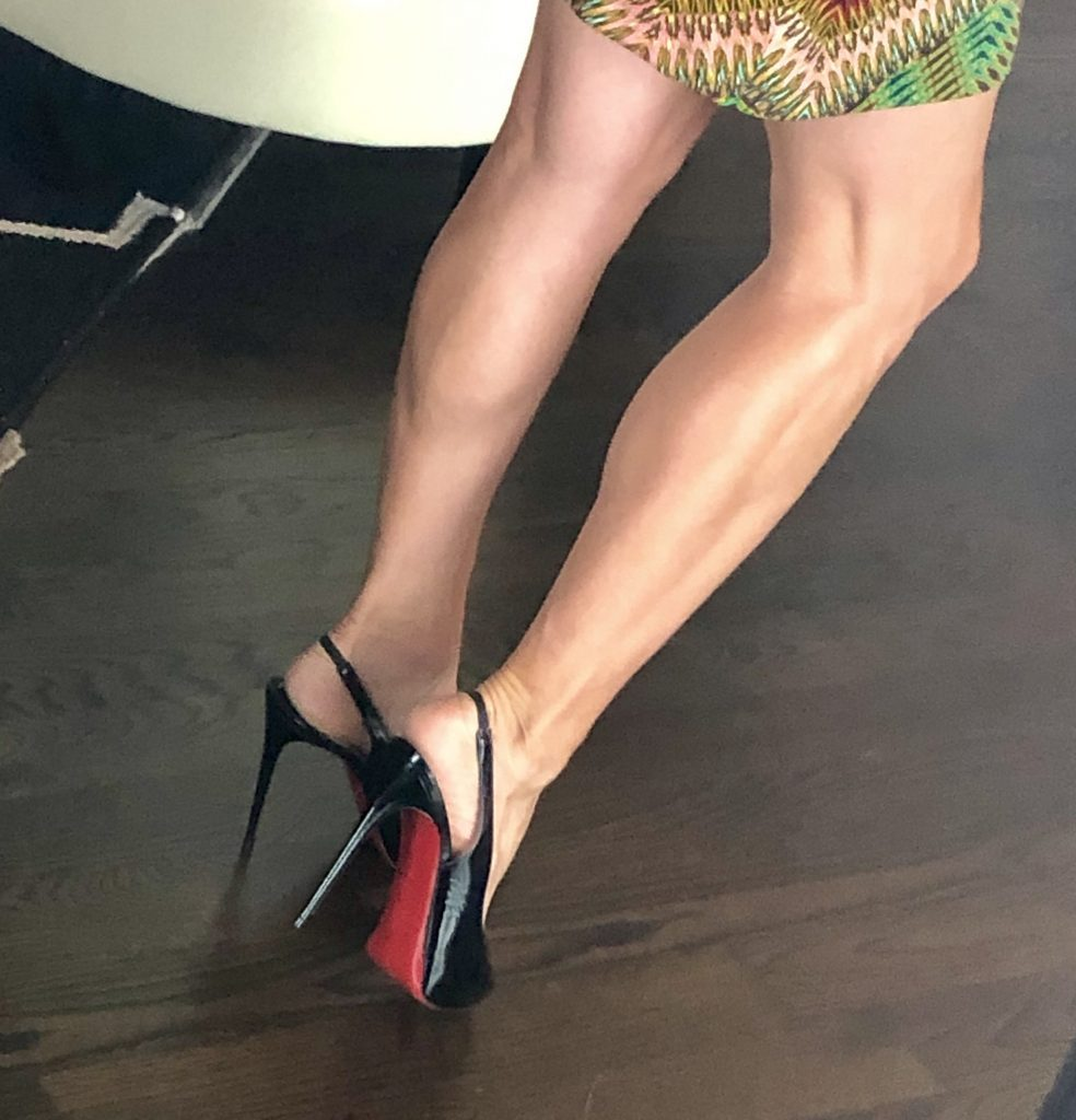 A ladies legs shown wearing a pair of patent leather stilettos. This pair by Christian Louboutin.