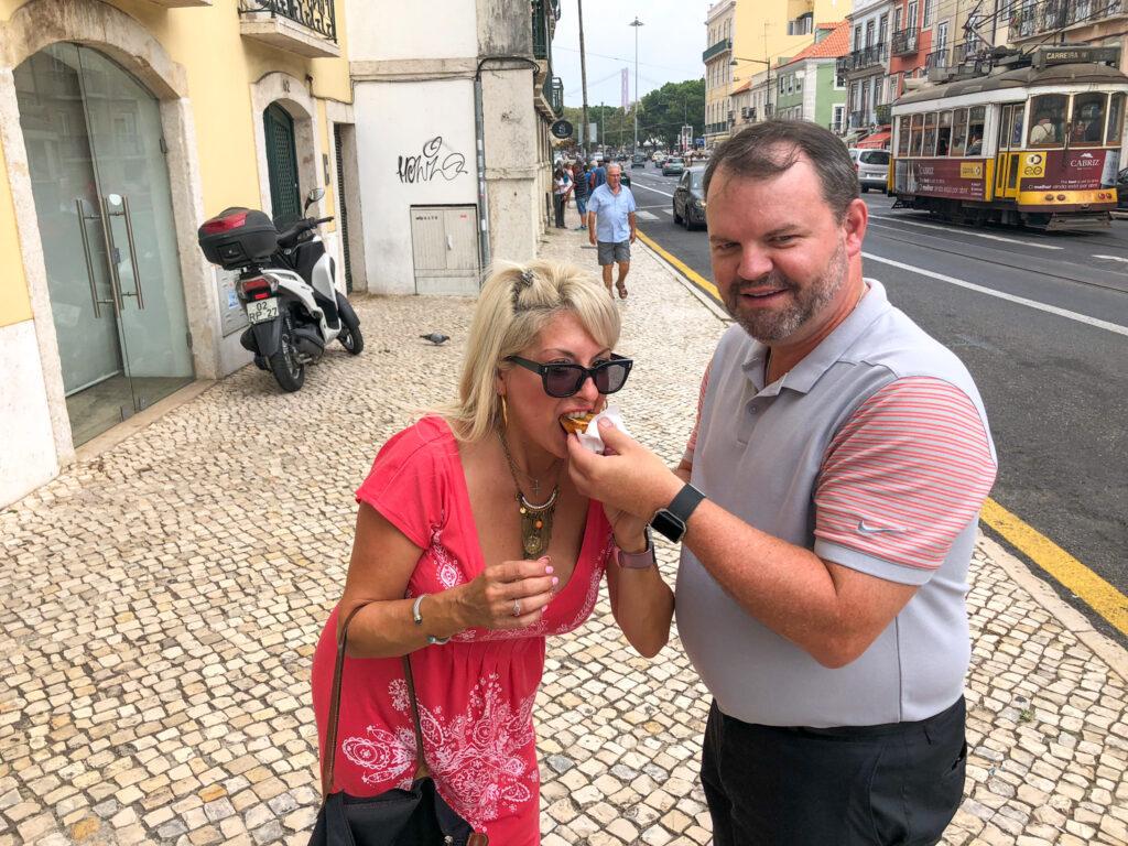 Maria on street in Belem, Lisbon in summer dress eating a pasteis de Belem