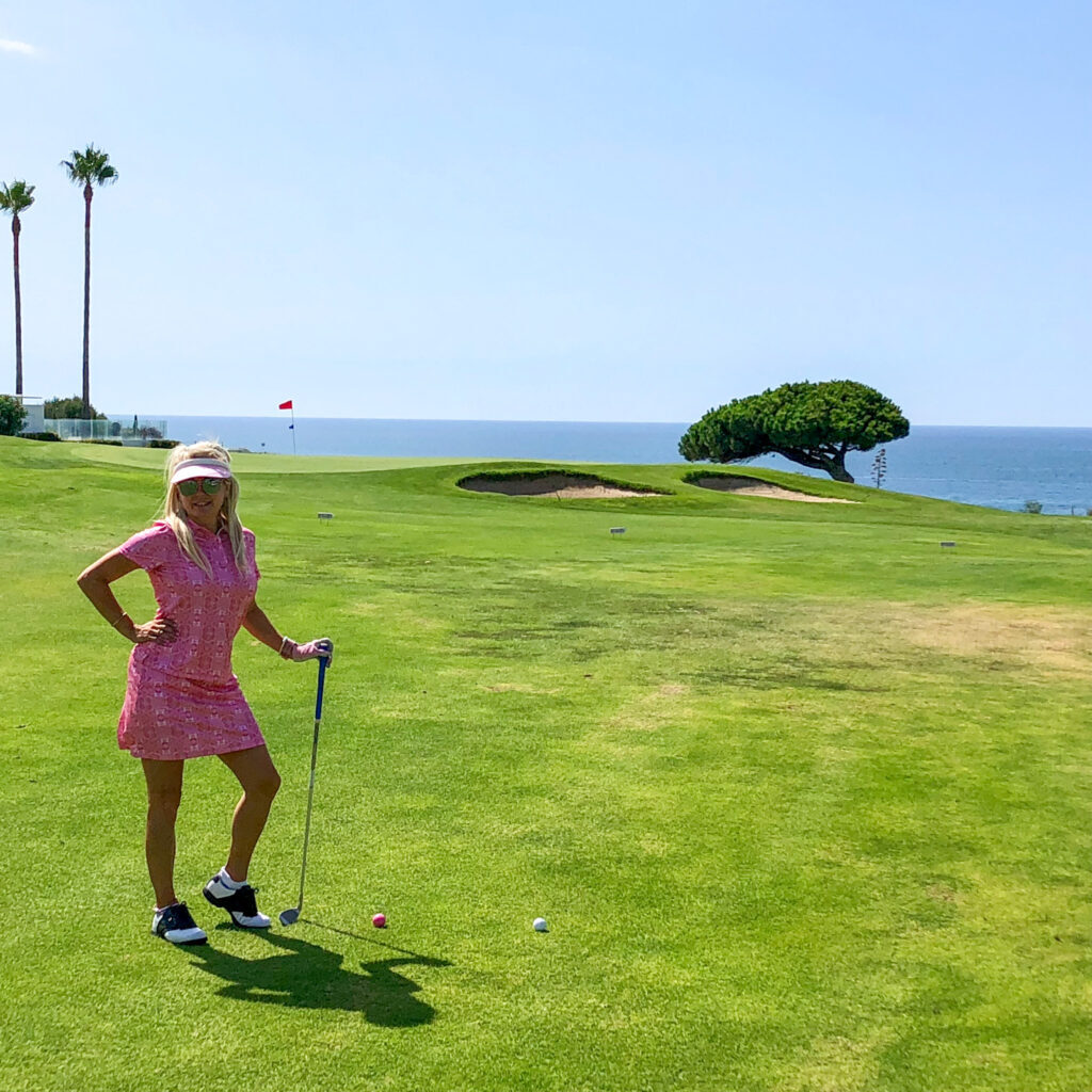 Girl posing with a golf club in golf outfit on an oceanside golf course